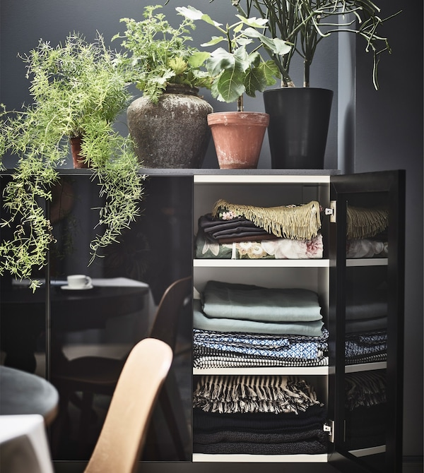 A black cabinet with smoky black glass doors opened to reveal linens.