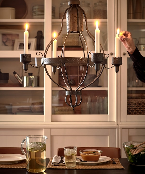 A black chandelier with four candles that are being lit by a person, a white glass-door cabinet and dinner served on a table.
