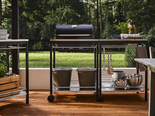 A black charcoal barbecue with trolley in stainless steel with kitchen utensils, bowls, bins with lids, herbs and oils.