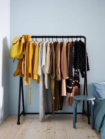 A black clothes rack with clothes hanging on it.