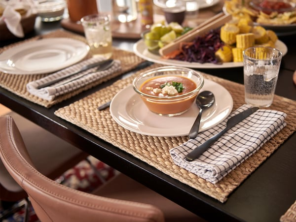 A black dining table with place mats made from water hyacinth, white plates, glass bowls with soup and folded tea towels.