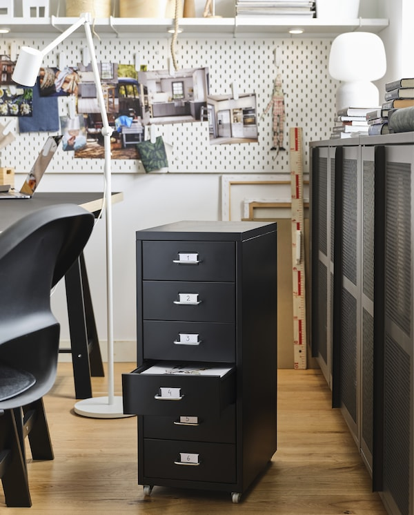 A black drawer unit on castors, grey cabinets with mesh doors, a white table lamp and white pegboards with photos on clips.