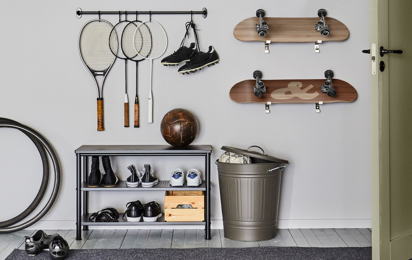 A black FINTORP rail holding a collection of hanging rackets on hooks, along with a few skateboards mounted to the wall.