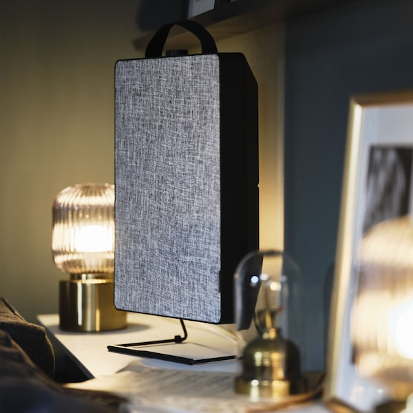 A black FÖRNUFTIG air purifier on a desk surrounded by gold accessories.