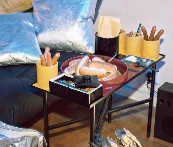 A black footstool with two silver-coloured cushions and a side table with modular tableware holding hotdogs and buns.