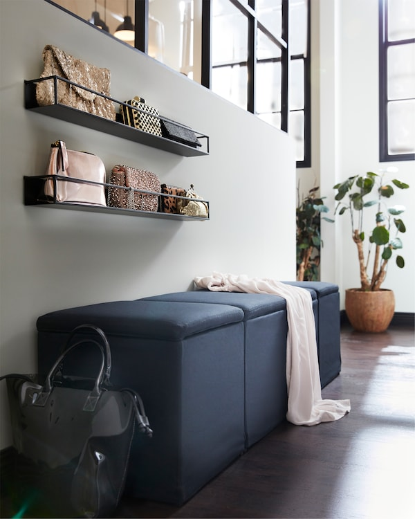 A black footstools with storage, black shelves with bags and a green plant.