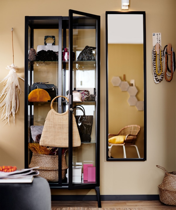 A black-framed glass display cabinet filled with bags and accessories next to a mirror.