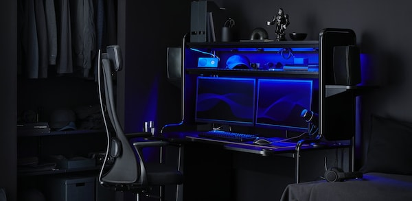 A black gaming desk holding two monitors with blue lighting surrounding the screens, with a black chair in front.