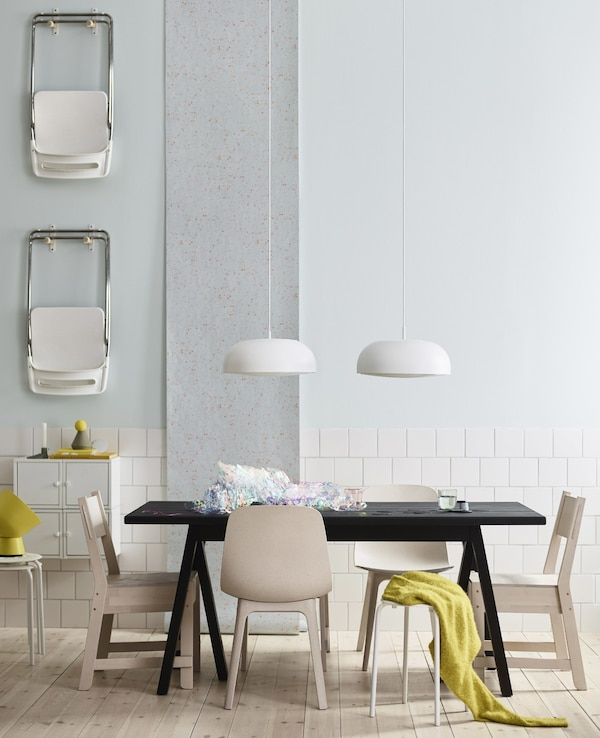 A black IKEA dining table with six different white and beige seats and two white pendant lamps hanging overhead.