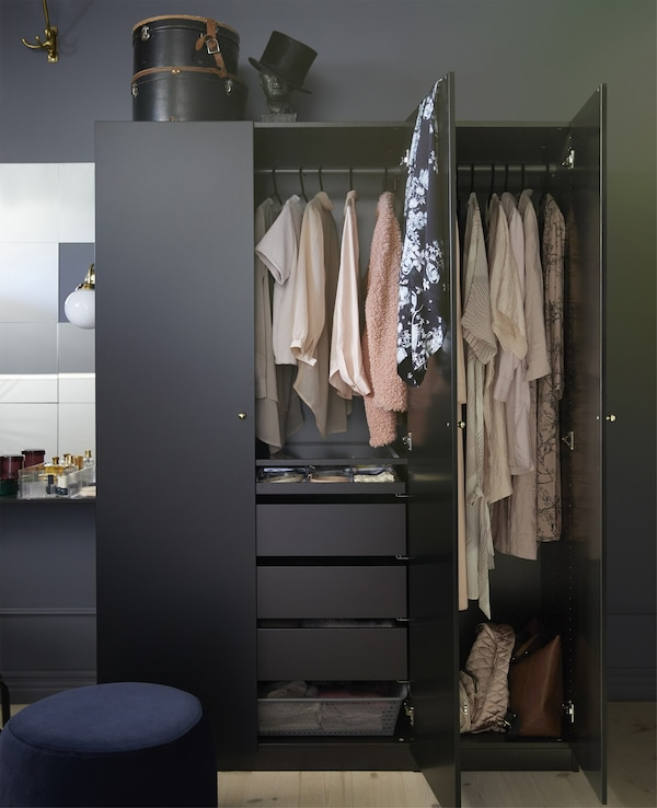 A black IKEA PAX wardrobe opened to reveal drawers and hanging clothes storage.