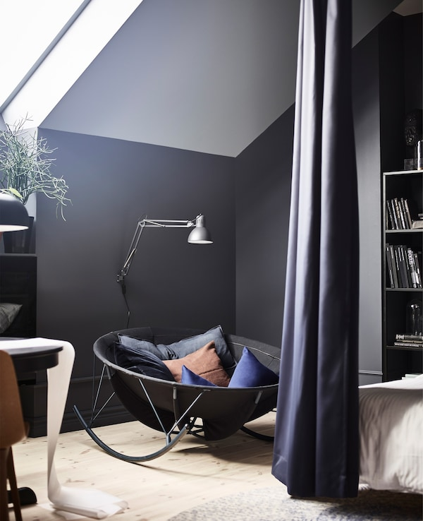 A black IKEA PS 2017 rocking-chair creates a reading corner in a bedroom with black walls.