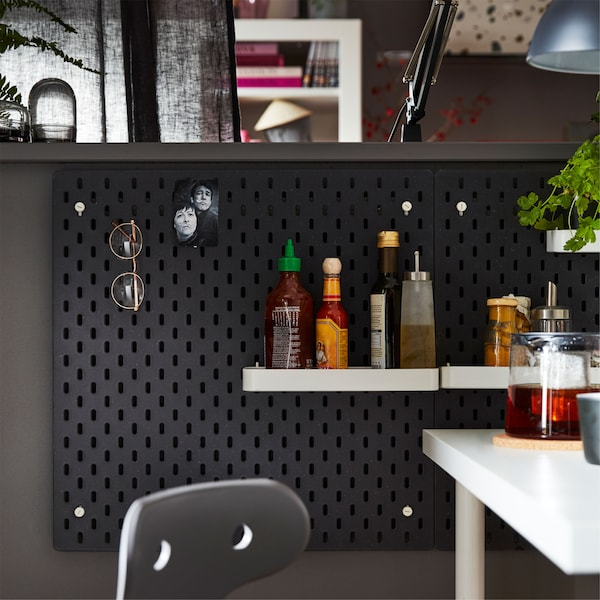 A black IKEA SKÅDIS pegboard and add-on white shelves and pegs, used to hang accessories and office and kitchen supplies.