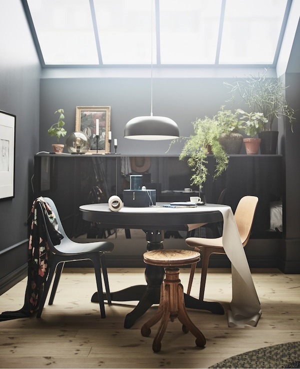 A black INGATORP extendable table creates an area to eat or work in this bedroom with skylights.