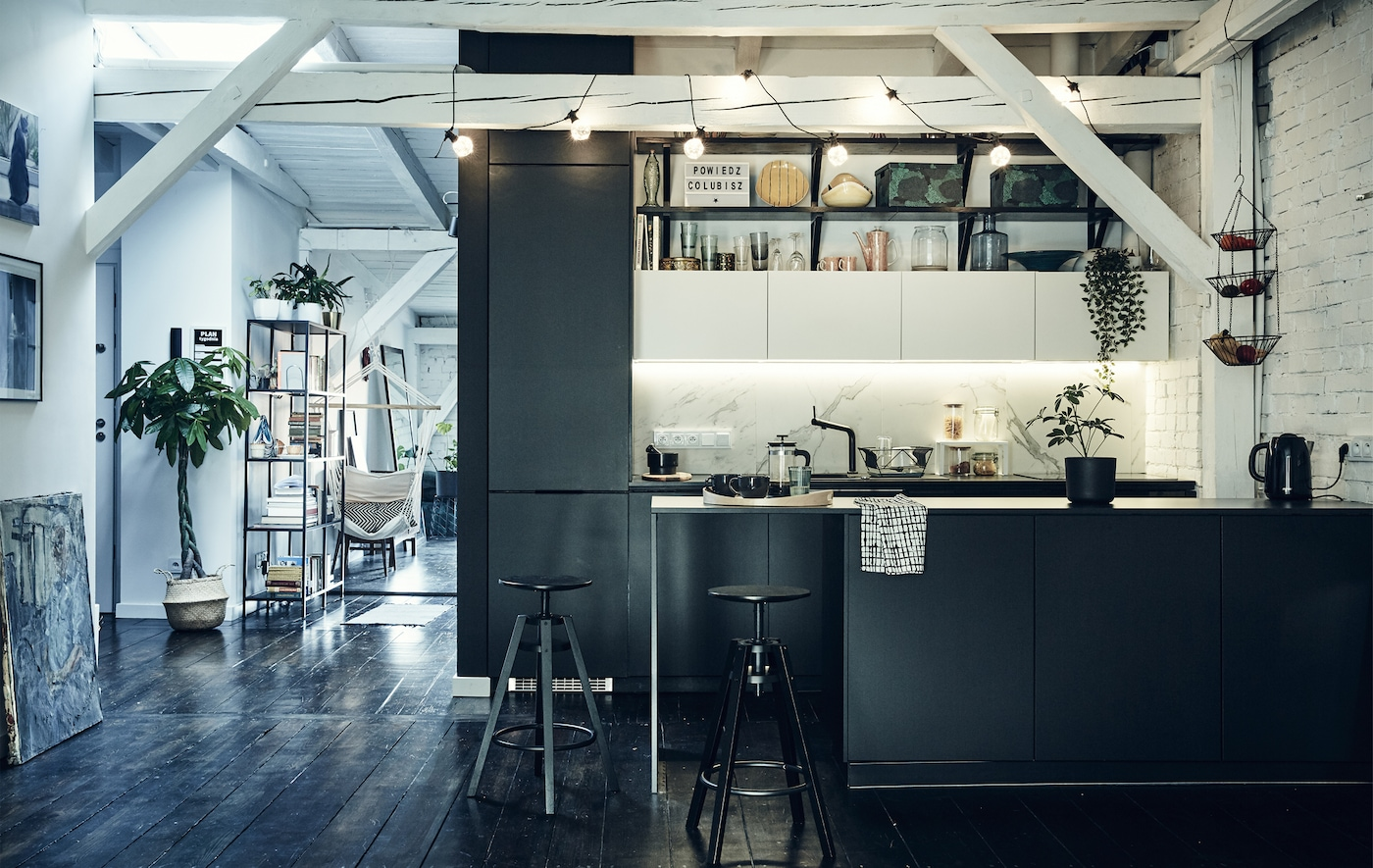 A black kitchen in an open-plan space with white beams across the ceiling and dark wooden floors.