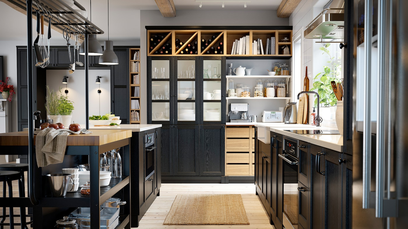 A black kitchen with a wooden floor, a black kitchen island, black cabinets and wine stored on open shelves.
