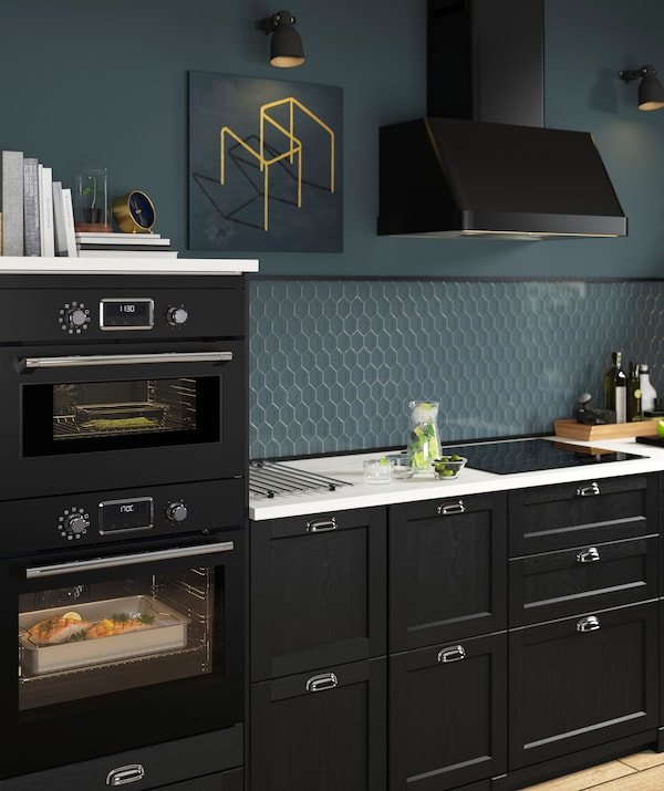 A black kitchen with blue walls, extractor hood, and built-in ovens.