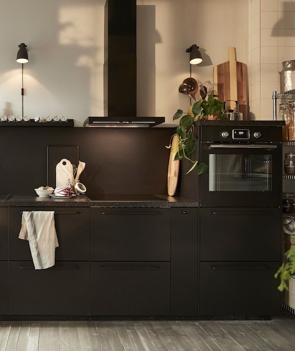 A black kitchen with extractor hood, built-in oven and dark worktops.