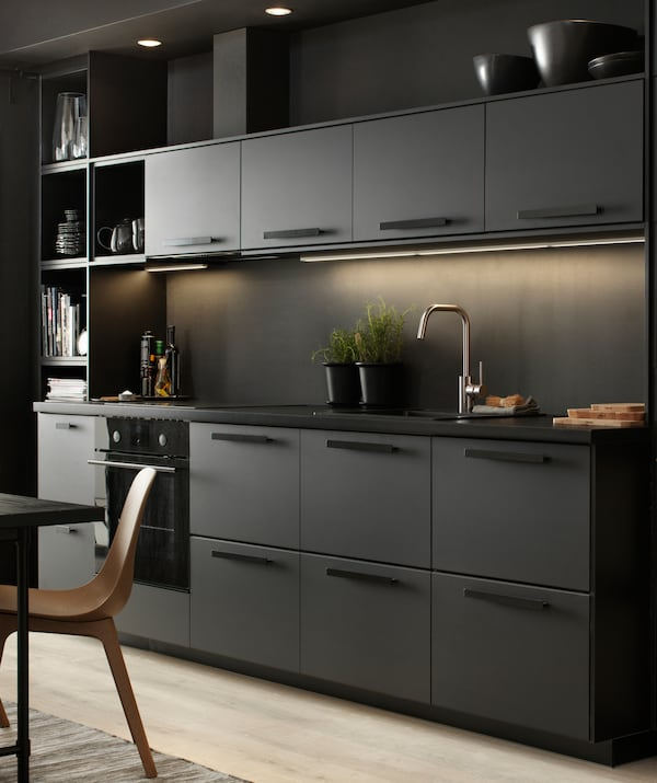 A black kitchen with lighting under the top cupboards.