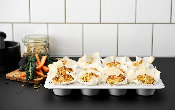 A black kitchen worktop with a VARDAGEN metal muffin tin filled with twelve muffins made with carrots and pumpkin seeds.