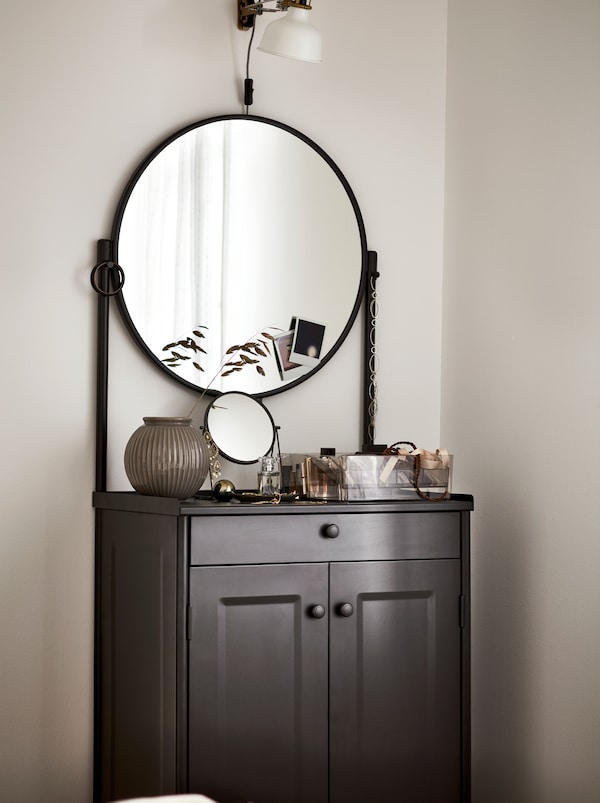 A black KORNSJÖ cabinet with a large, round mirror, displaying decorative objects and a white lamp placed above it.