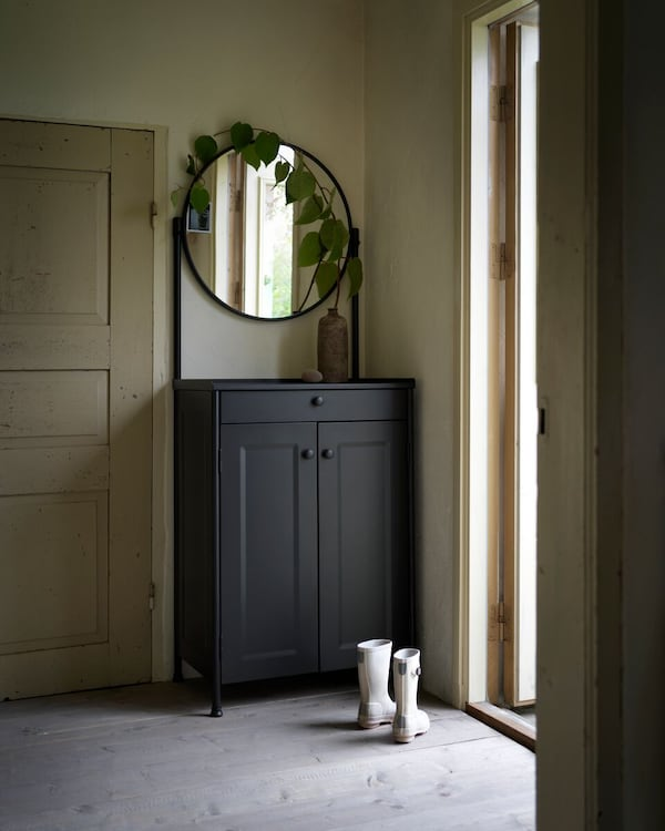 A black KORNSJÖ cabinet with mirror standing in a hallway with boots beside it.