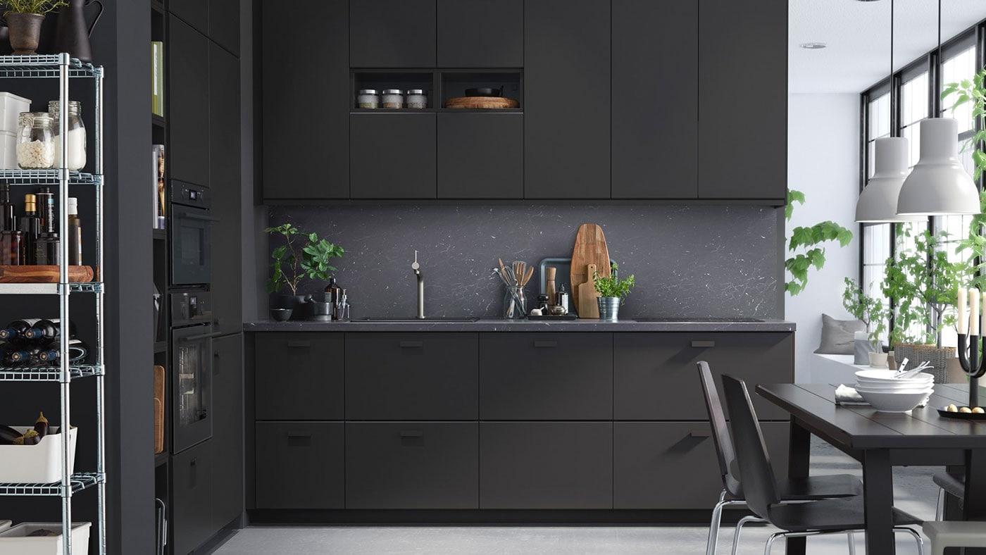 A black KUNGSBACKA kitchen with dark worktop and black, slimline handles.