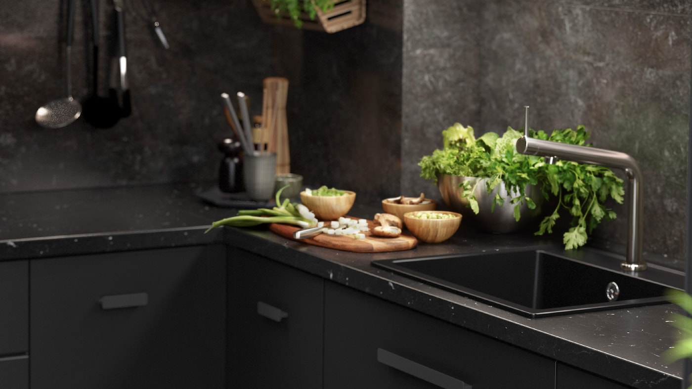 A black KUNGSBACKA kitchen with marble inspired features with kitchen utensils and fresh herbs.