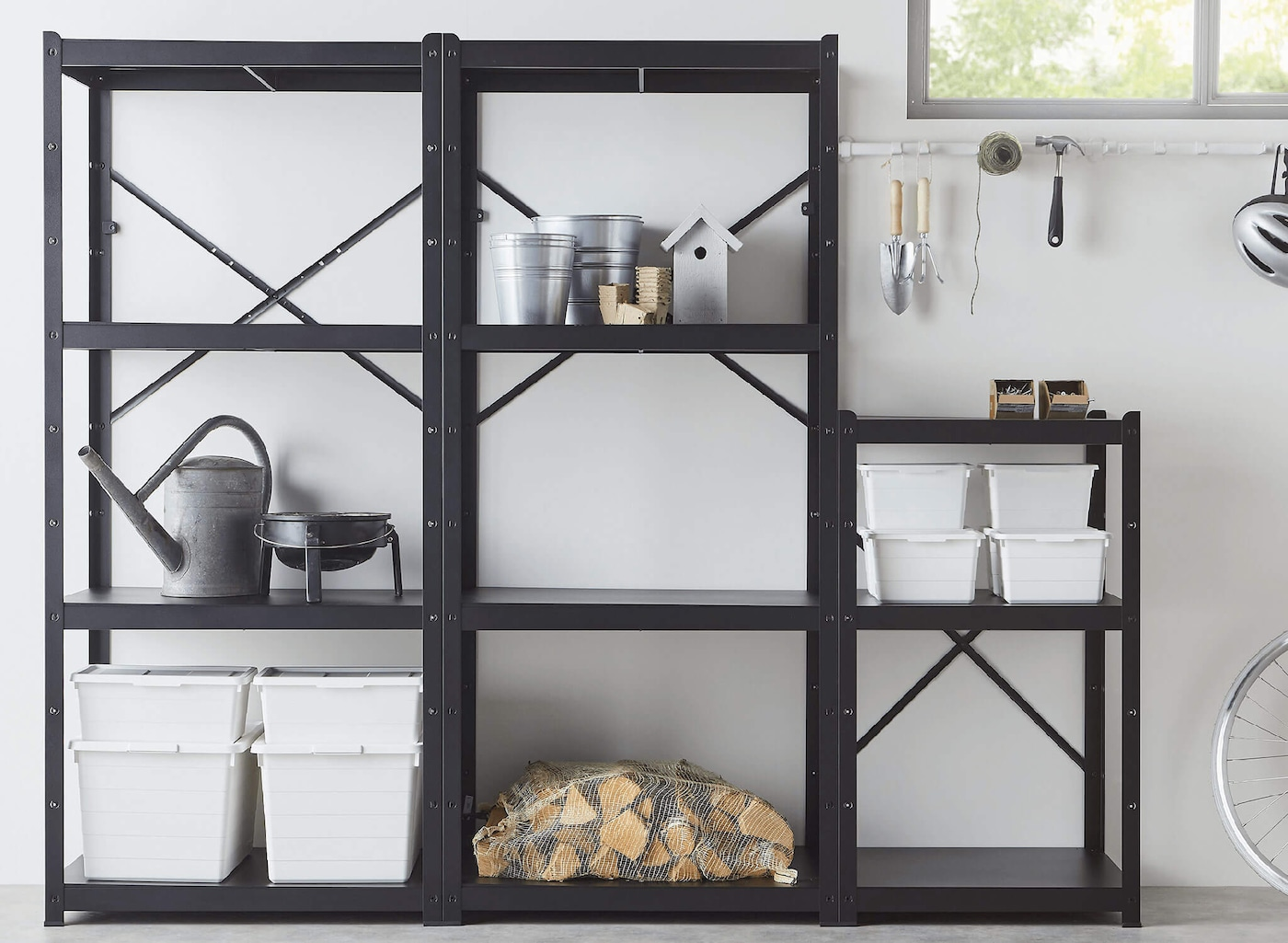 A black metal shelving system with three sections, housing storage boxes, a watering can, and firewood against a white wall.