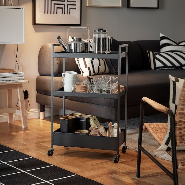 A black NISSAFORS trolley with a kettle, mugs and tea bags on its shelves is standing next to a sofa and armchair.