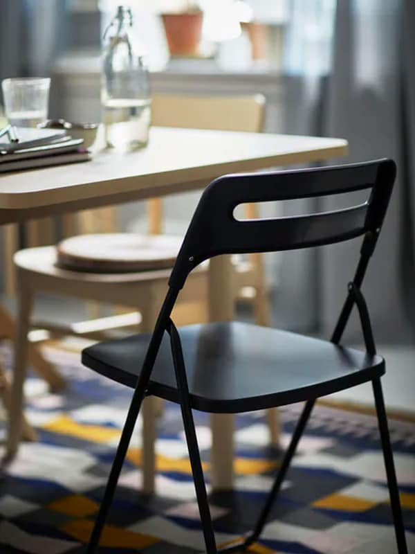 A black NISSE folding chair placed beside a RÖNNINGE birch chair by a RÖNNINGE birch table, all standing on a TÅRBÄK rug.
