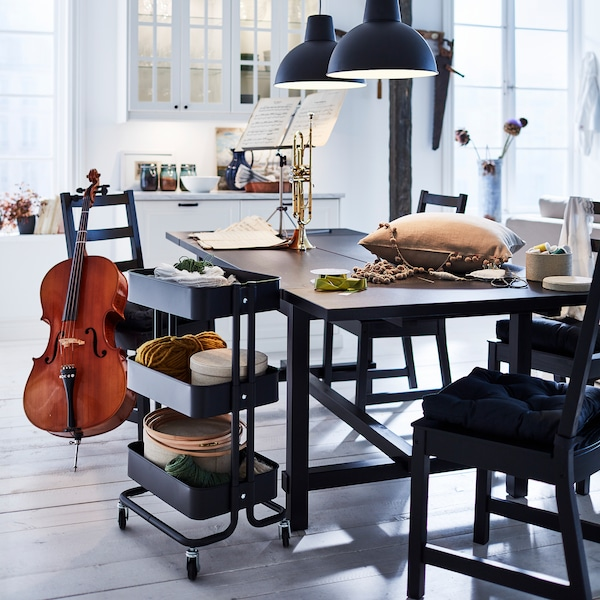 A black NORDVIKEN extendable table is extended to create extra table surface for crafts, music and hobbies.