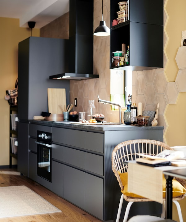 A black one-wall kitchen with an extractor hood mounted on the wall in a room painted soft yellow.