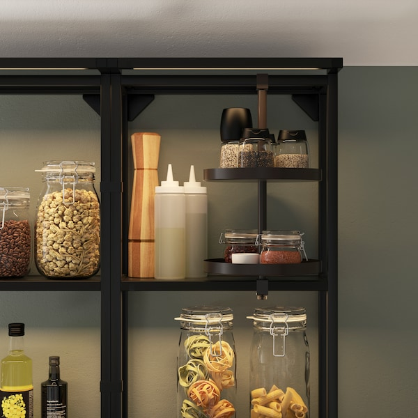 A black open shelf with integrated lighting, a swivel shelf, glass jars with pasta, different spice jars, oils and dressings.