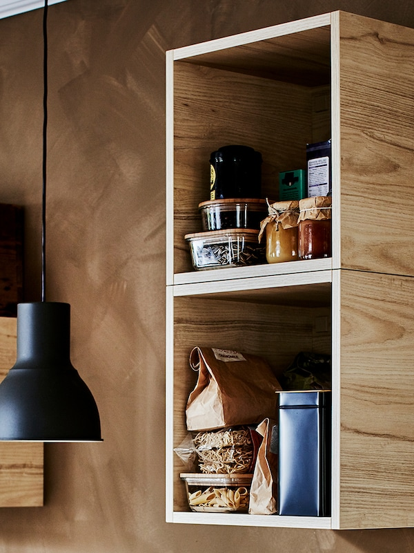 A black pendant lamp hangs next to two, TUTEMO open cabinets mounted vertically on a wall, various food containers inside.