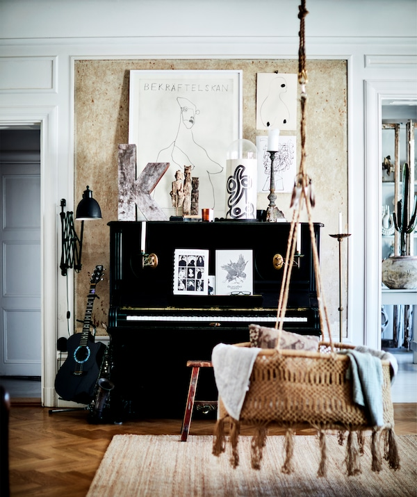 A black piano and a hanging rattan seat in a room with wooden floor.