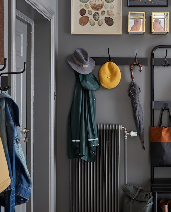 A black rack with three hooks is wall-mounted over a radiator. An umbrella, two hats and a rain jacket hang on the hooks.