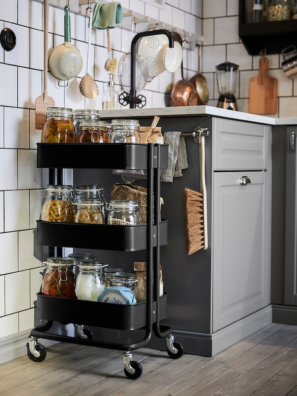 A black, RÅSKOG trolley, with glass jars of various foods on its shelves, stands next to a sink in a white-tiled kitchen.