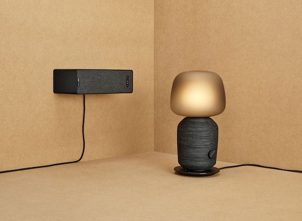 A black rounded speaker lamp next to a black wall mounted speaker.