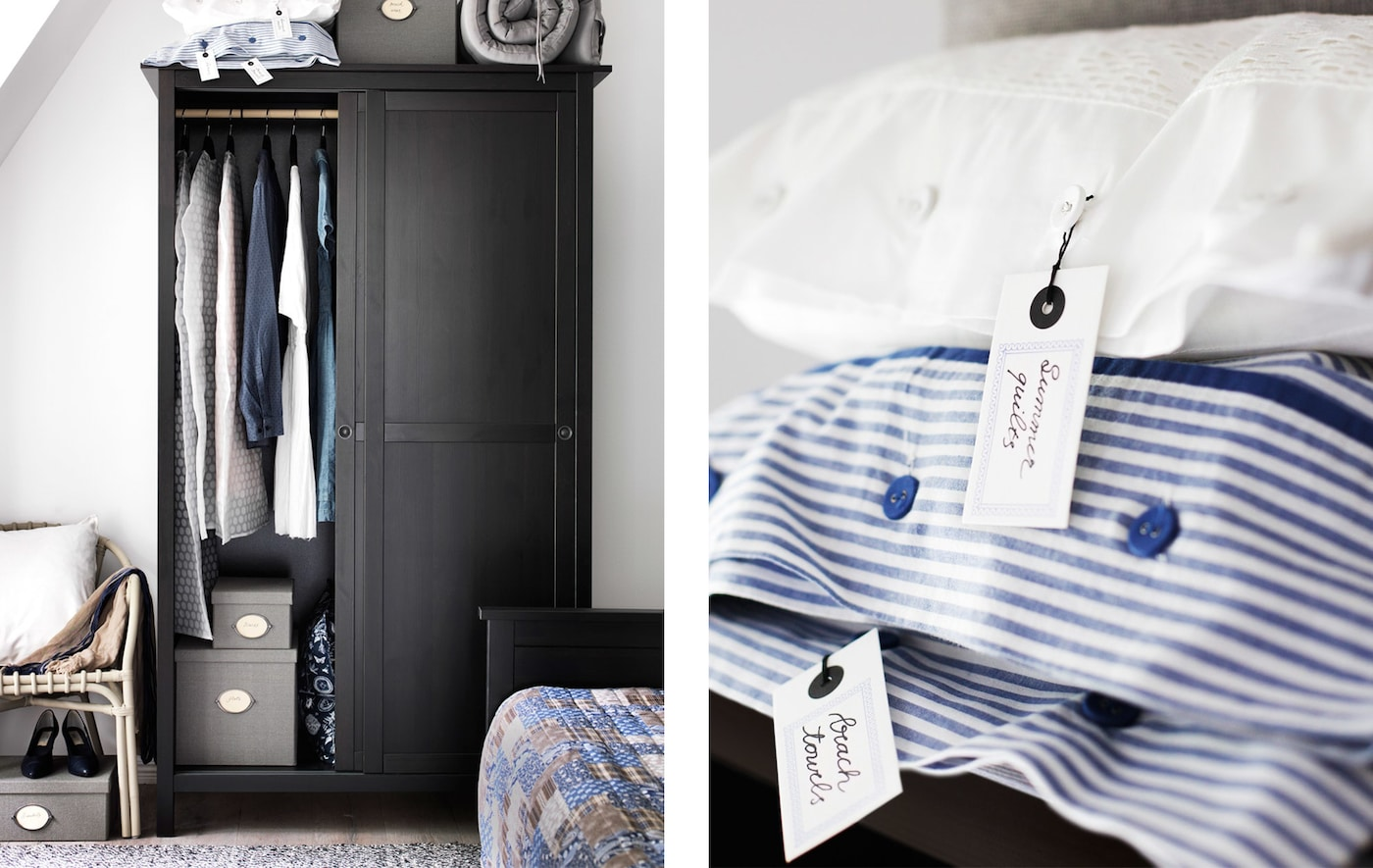 A black rustic style wooden wardrobe in the corner of a bedroom filled with clothes will storage boxes and bedding stacked on top next to an image of a close-up of some white and blue and white stripped pillow cases.