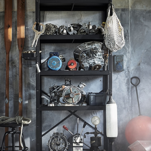 A black shelf used to store automotive parts, in a garage space.