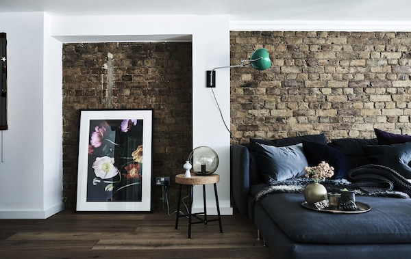 A black sofa against an exposed brick wall, next to a large picture leaning against the wall.