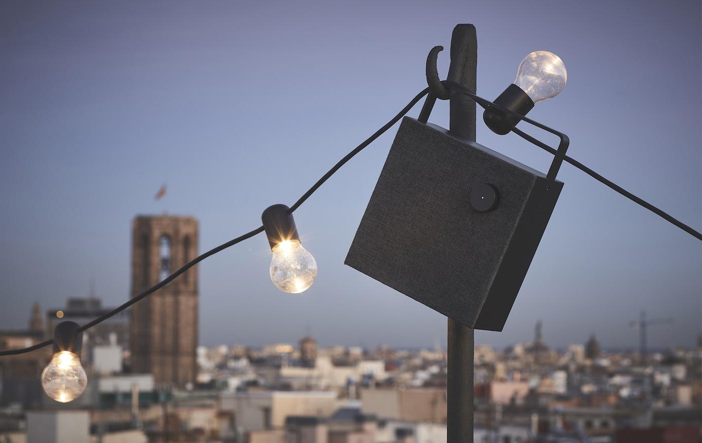 A black speaker and string of lights hanging up outside.