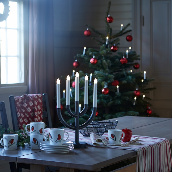 A black STRÅLA 5-armed LED candelabra is on a table in a dimly lit kitchen setting with a decorated tree in the background.