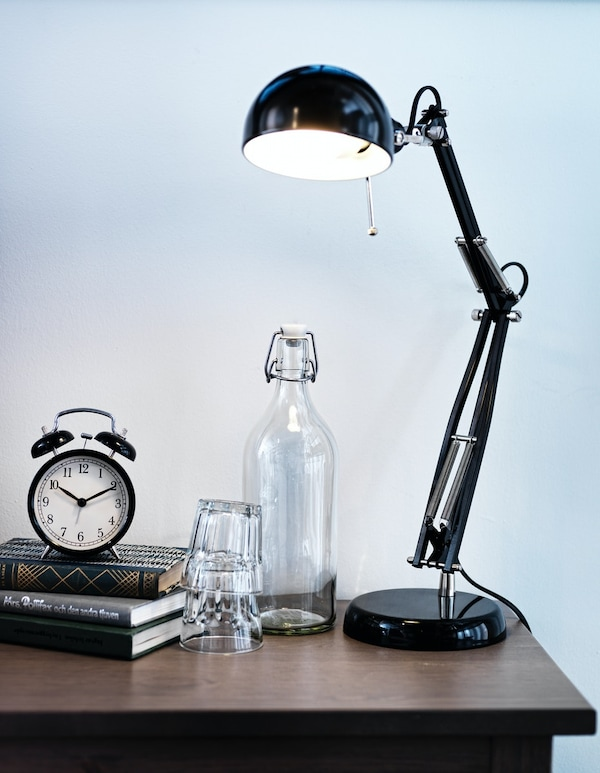 A black study lamp on a table along with books, alaram, and glassware