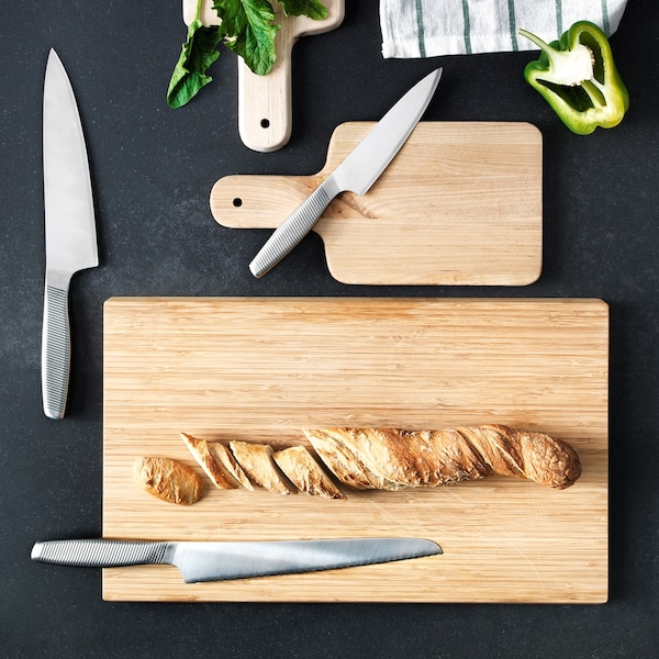 A black surface holding three wooden chopping boards and three kitchen knives. A loaf of bread is on one chopping board.