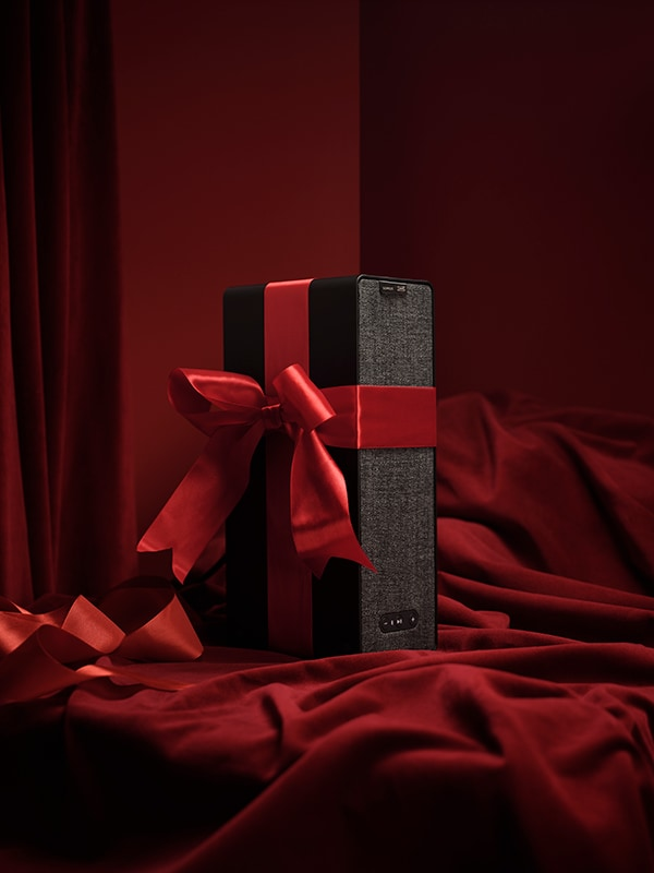 A black SYMFONISK speaker wrapped with a red ribbon