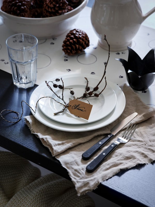 A black table is set with light-colored dinnerware and natural accessories, including pine cones and sticks.