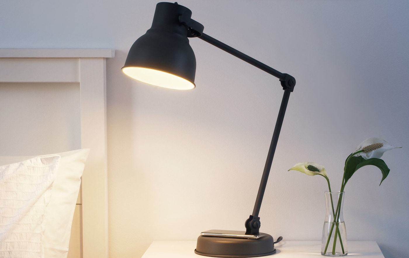 A black table lamp on a bedside table.