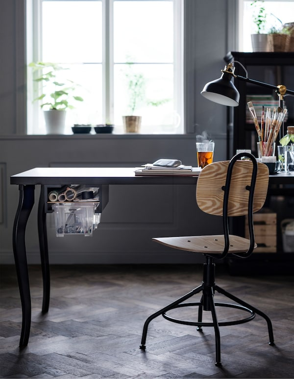 A black table with a DIY drawer is being used as a desk for a home office workspace.