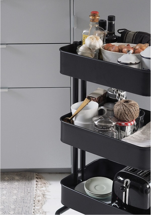 A black trolley with three storage shelves.